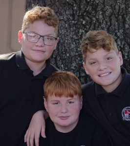 Three brothers smiling at camera