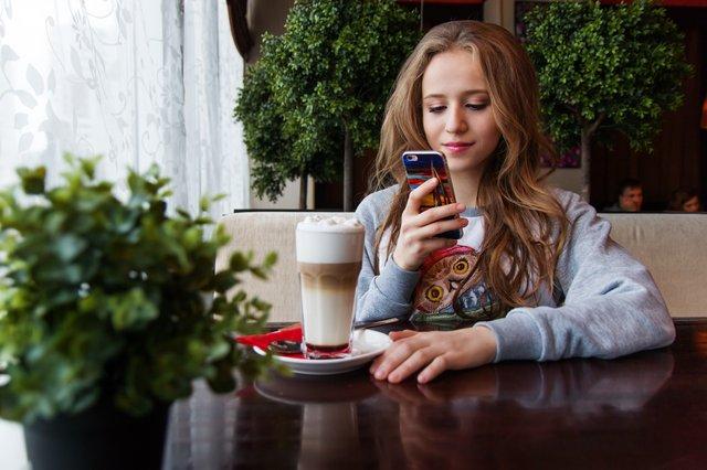 teen on phone with coffee