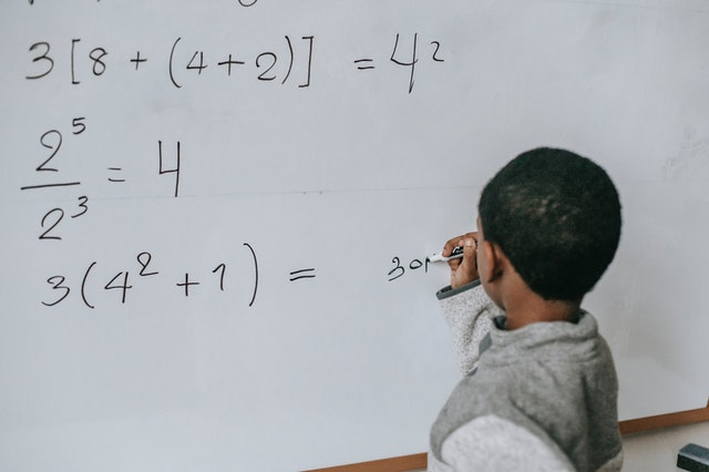 child doing math on whiteboard