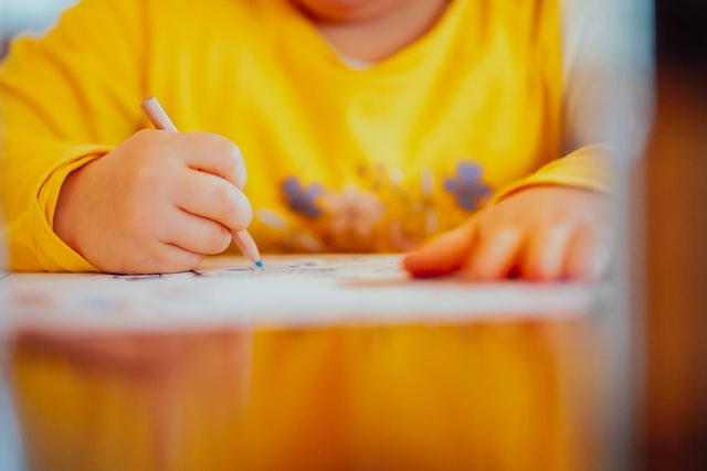 child in yellow shirt drawing a picture