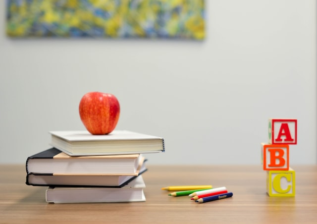 desk with books apple and pencils