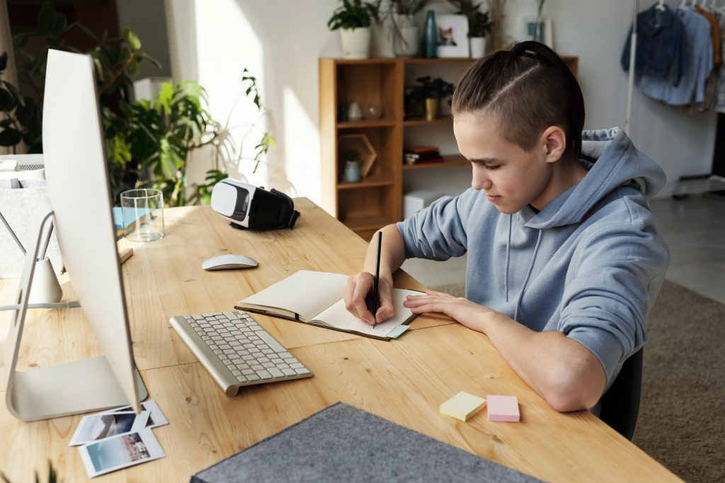 boy studying at desk with notebook and computer