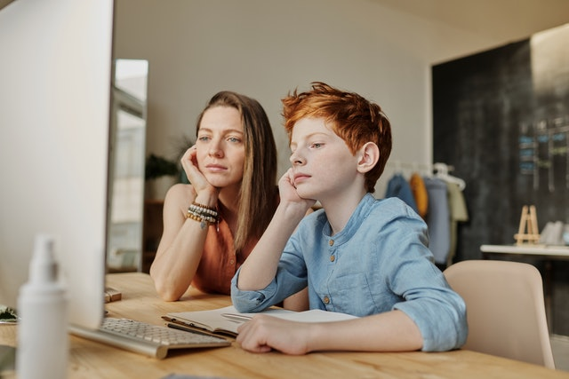 woman and red haired boy at desk looking at computer