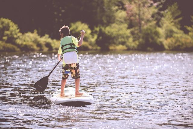 boy with life jacket paddle boarding on lake