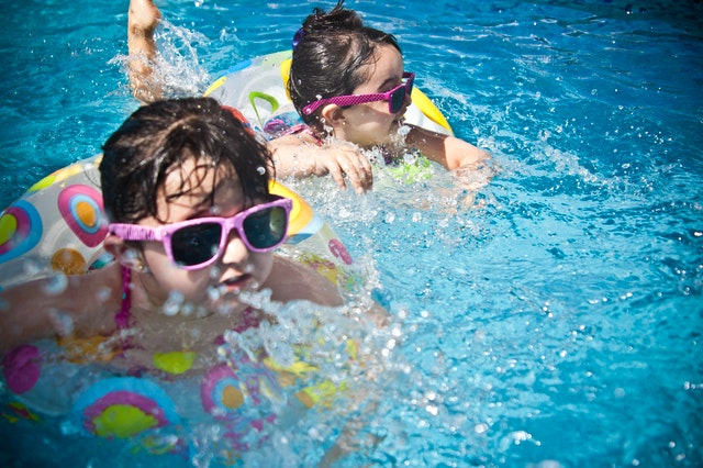 swimming children in pool with sunglasses