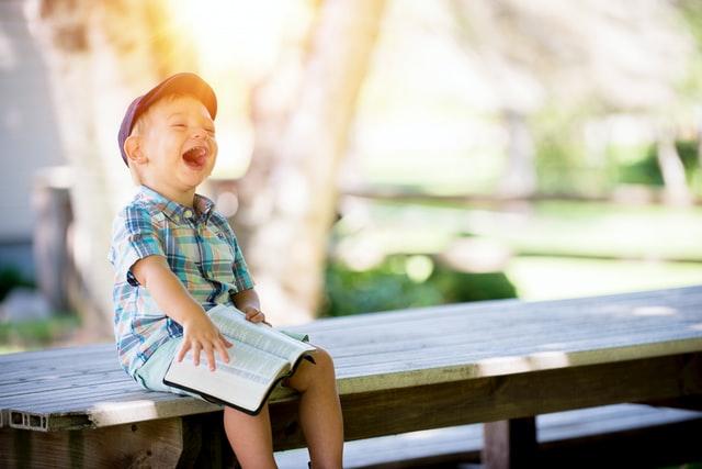 boy wearing hat laughing while holding Bible