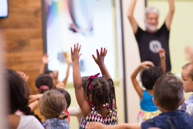 children with hands in air and teacher